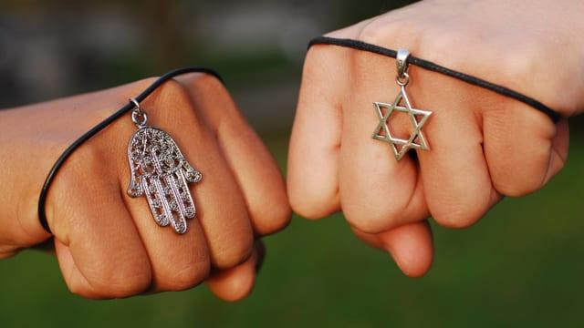 Zwei Hände zeigen die religiösen Symbole Hand der Fatima und Davidstern.