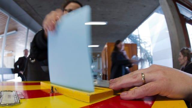 Gelb-rot gestreifte Abstimmungsurne. Eine Stimmbürgerin wirft einen Abstimmungszettel ein.