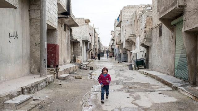 kleines Mädchen springt auf Strasse zwischen zerbombten Häusern