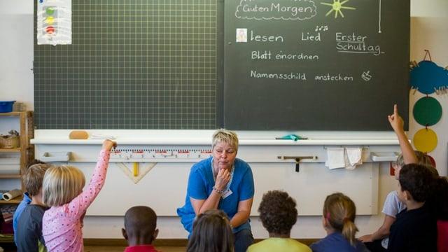 Kinder und eine Lehrerin vor der Wandtafel im Schulzimmer.