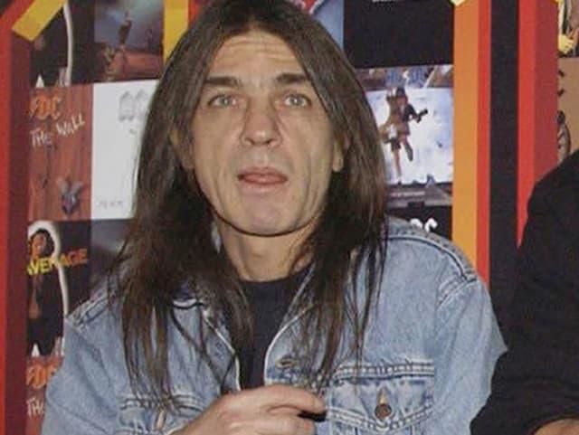 Malcolm Young in Jeansjacke vor einer Bilderwand mit AC/DC-Covern