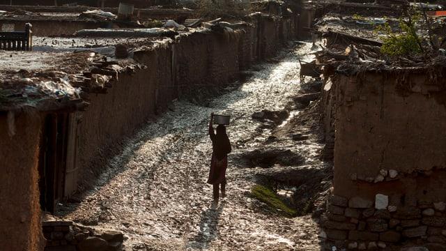 Mädchen trägt Wasser in Slum