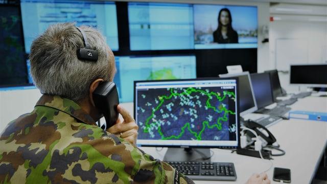 Telefonierender Mann am Computer. Vor sich auf dem Bildschirm eine Schweizer Karte.