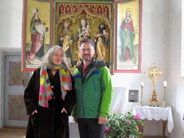Eine Frau und ein Mann vor dem Altarbild in einer Kapelle