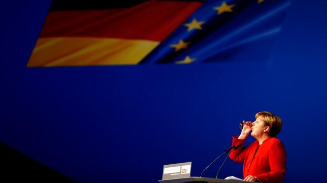 Merkel am Rednerpult, sie trinkt aus einem Glas Wasser.