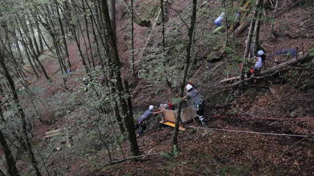 Die abgestürzte Transportkiste wird im steilen Waldgebiet geborgen.