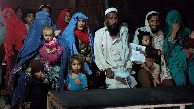 Afghanische Vertriebene, kniend in einem Zelt.