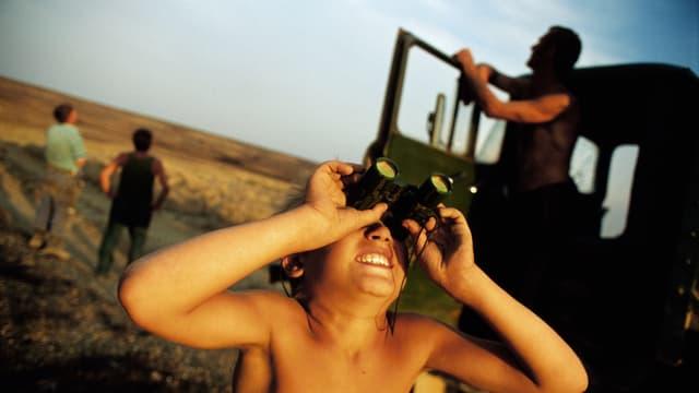 Ein Junge schaut mit dem Feldstecher in den Himmel.