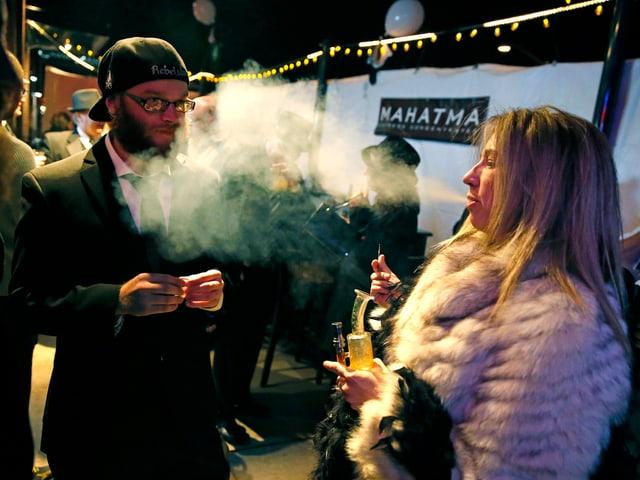 Zwei Personen rauchen einen Joint.