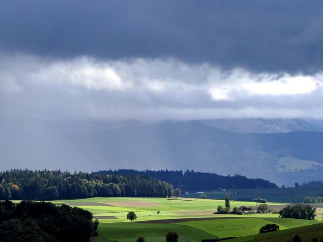 Durch die Lücken in den Regenwolken dringt Sonnenlicht hindurch.