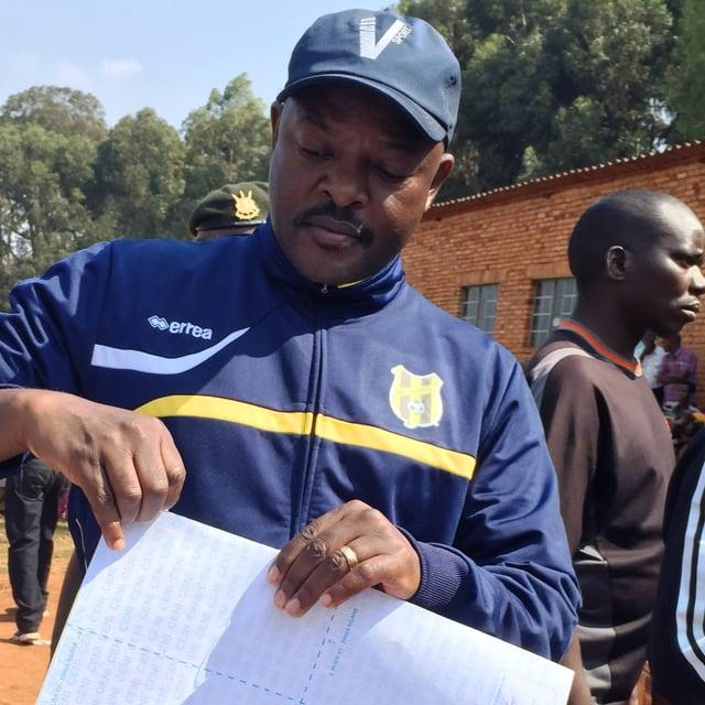 Ein Afrikaner in blaubem Trainingsanzug und Baseball-Mütze mit einem Bogen weissen Papiers in der Hand, um ihn herum stehen weitere Menschen.