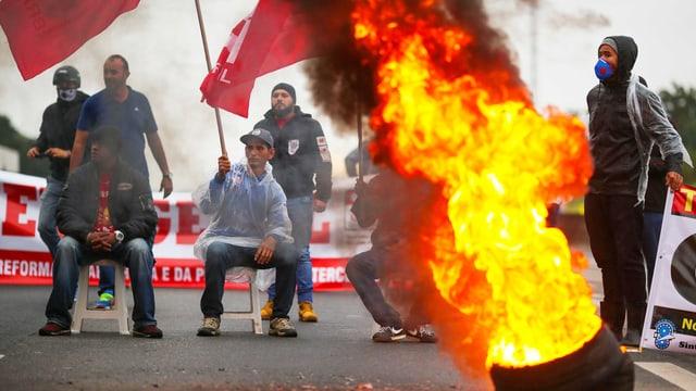 Demonstranten neben Strassenbarrikaden