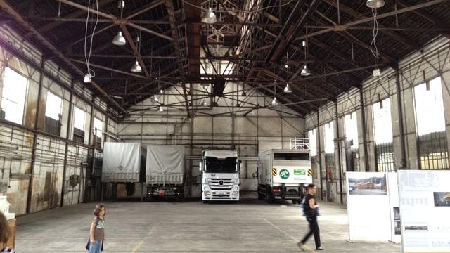Im Innern stehen zwei Lastwagen und zwei Anhänger, zudem Tafeln die über das Projekt informieren. Von der Decke hängen mehrere Lampen und Kabel. Die Wände sind teils mit Flecken bedeckt. Im Vordergrund sieht man ein Kind und eine erwachsene Person, die sich im Gebäude bewegen.