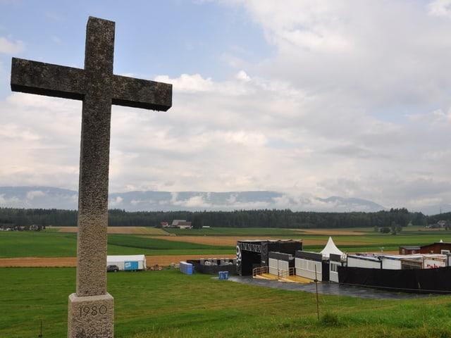 Ein Wegkreuz, im Hintergrund weisse und schwarze Zelte.