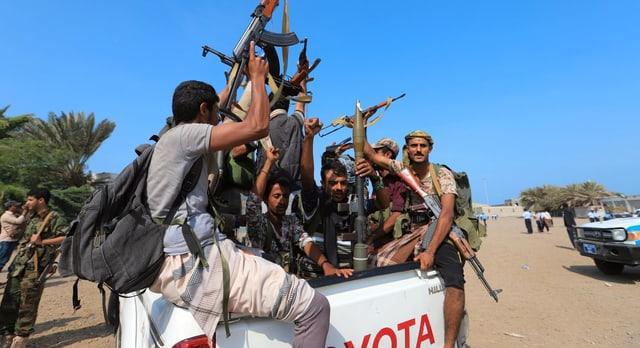 Symbolbild: Huthi-Rebellen in Jemen sitzen auf einem Pickup und präsentieren ihre Waffen.