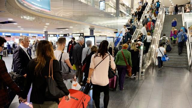 Schlangen von Reisenden vor den Rolltreppen im Flughafen Zürich