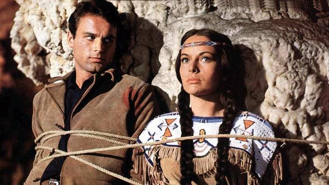 Ein Mann und eine Frau sind mit Seilen an einen Felsen gefesselt. Er trägt eine Lederjacke, sie ein Lederoberteil mit Fransen, ein Stirnband und Zöpfe.