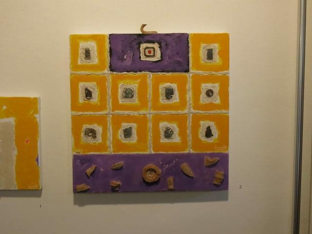 Auf dem Bild sind 12 gelbe Quadrate, in die jeweils eine Scherbe oder ein Stück Metall eingearbeitet ist.