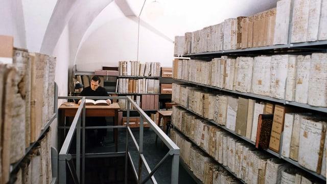 Ein Geistlicher sitzt in den vatikanischen Archiven.