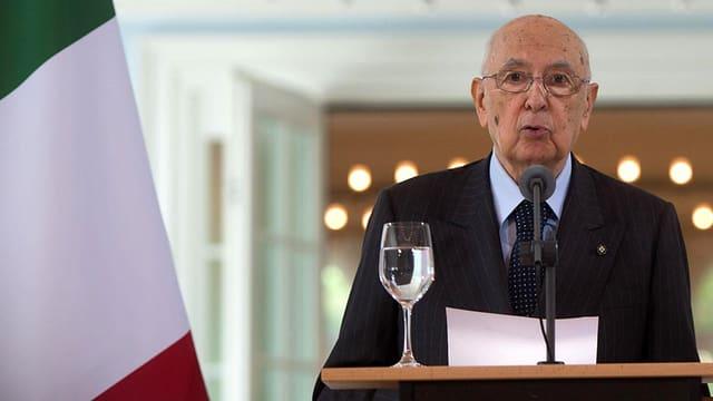 Giorgio Napolitano an einem Rednerpult neben einer italienischen Fahne.