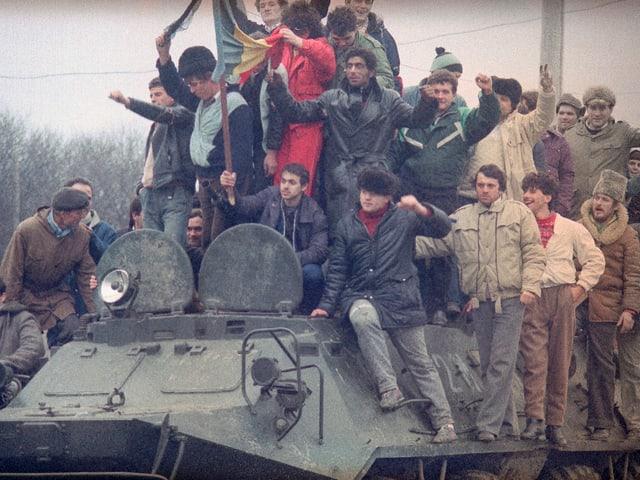 Zivilisten auf Panzer sitzend und stehend