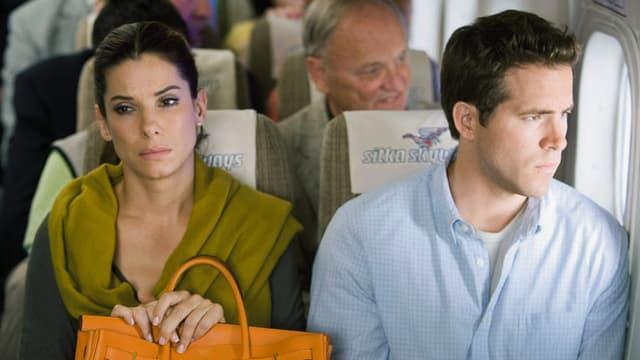 Eine Frau und ein Mann sitzen nebeneinander im Flugzeug.