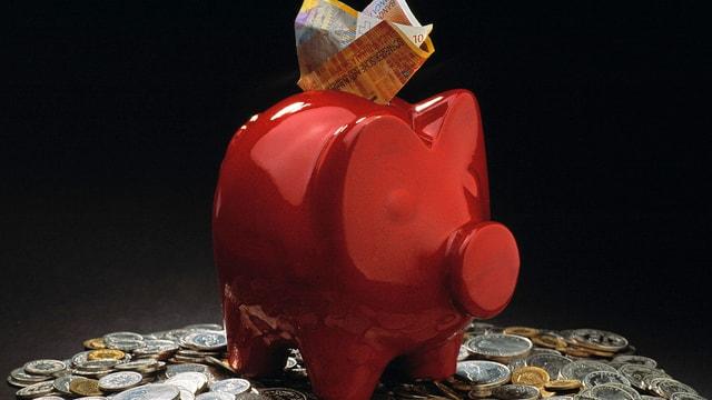 Rotes Sparschwein auf Geldmünzen.