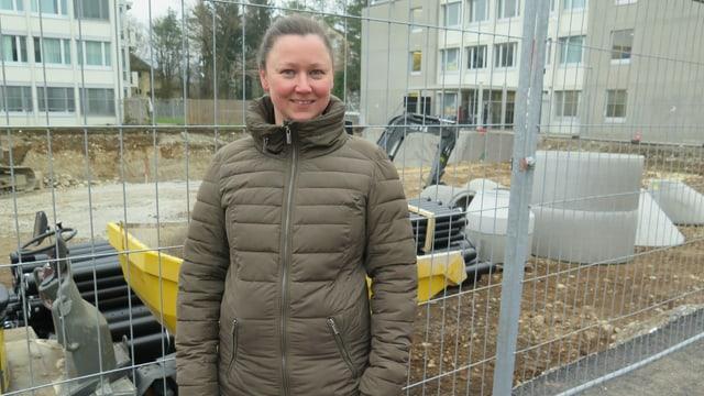 Frau in Mantel vor Baustelle