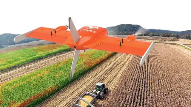 Unbemanntes Flugzeug in der Luft, unten ein Traktor auf einem Feld.