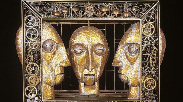 Ein Kunstwerk aus drei goldenen Köpfen.