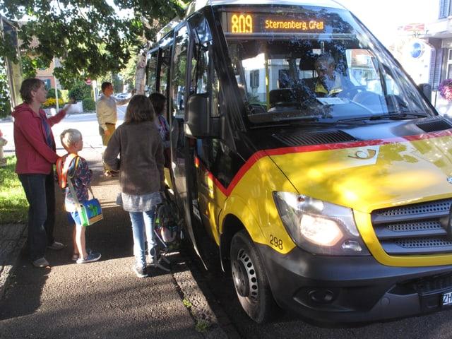 Das Postauto wartet am Trottoirrand, Kinder steigen ein, eine Mutter steht draussen und winkt.