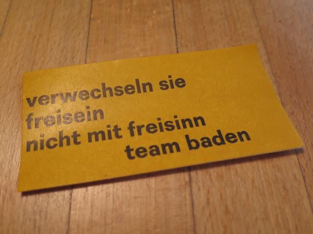 Gelber Kleber mit Aufschrift auf Holztisch.