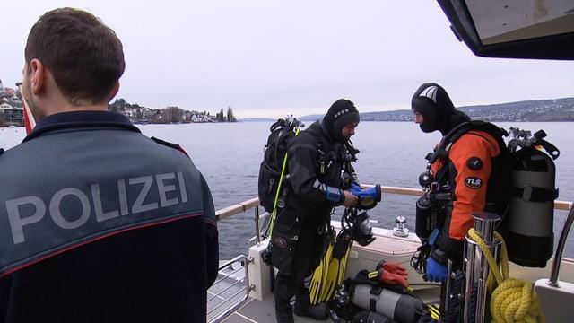 Zwei ausgerüstete Polizeitaucher an Deck ihres Bootes bei der Vorbereitung des Tauchgangs.