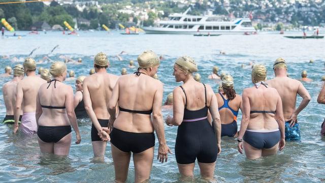 Männer und Frauen in Badekappen im See.