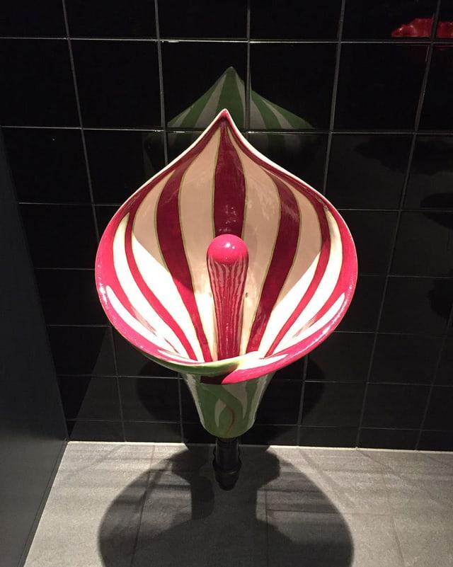 Pissoir in Form einer weiss-rot-gestereiften Blume.