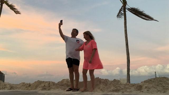Duas persunas che fan ina fotografia dad els cun davostier la riva da la mar.