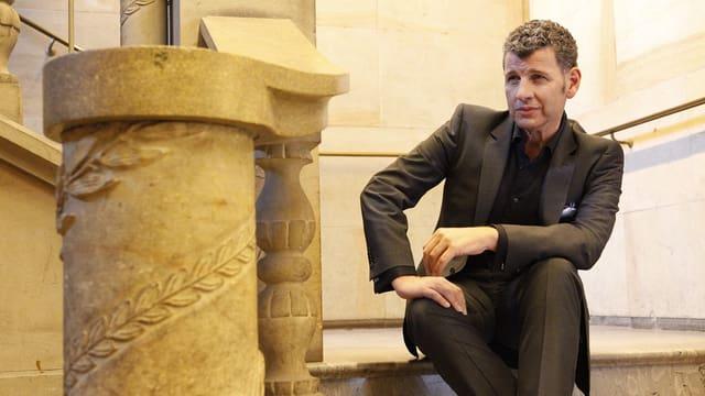 Semino Rossi in einem Anzug sitzt auf einer Treppe neben antiken Säulen.