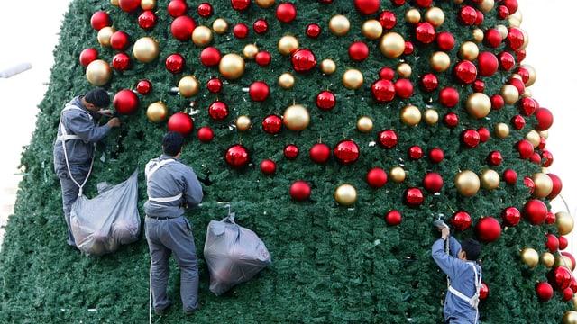 Drei Arbeiter dekorieren einen riesigen Weihnachtsbaum in Peking mit roten und goldenen Kugeln.