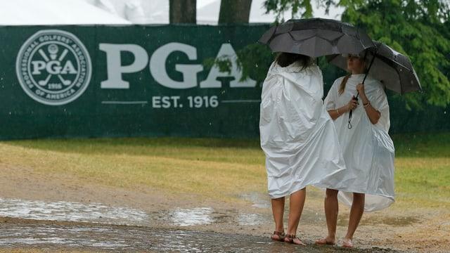 Zwei Zuschauerinnen schützen sich auf dem Golf-Course vor dem Regen.