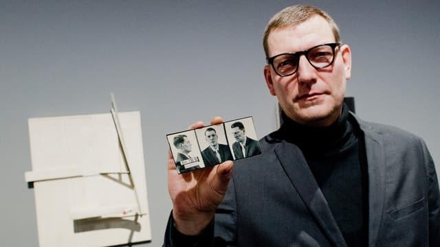 Ein Mann steht vor einem abstrakten Relief. Er hält schwarz-weisse Porträtfotos in der Hand.
