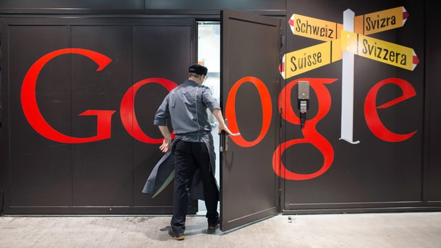 Ein Mann betritt ein Gebäude von Google. Das Logo steht in grossen, roten Buchstaben auf dem Eingang.