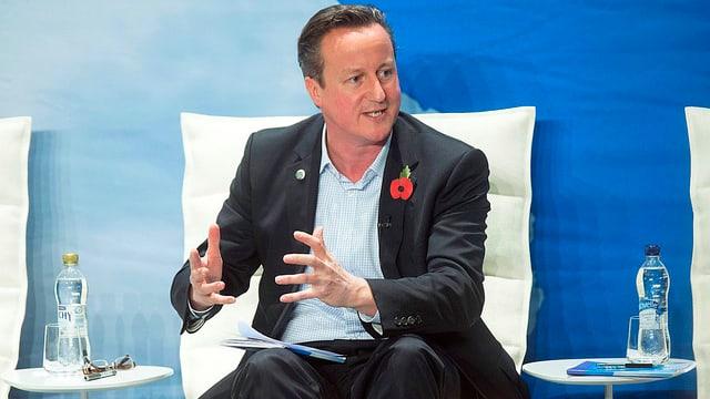 David Cameron, auf Sessel sitzend und mit den Händen gestikulierend.