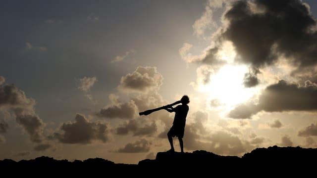 Australischer Ureinwohner auf einem Felsen im Gegenlicht, er spielt Didgeridoo.