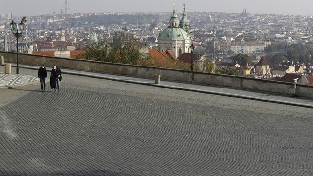 Die Plätze sind leer: zwei Menschen laufen über den sonst vollen Platz vor dem Prager Schloss.