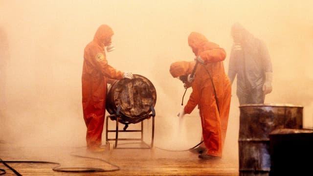 Männer in orangenen Anzügen stehen in gelbem Nebel um ein Fass. Einer spritzt den Boden ab.