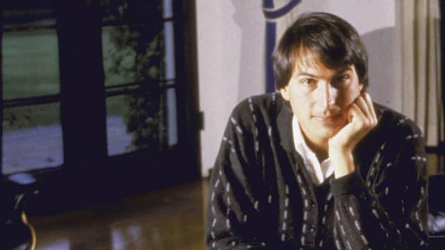 Steve Jobs guckt, auf die Hand gestützt, in die Kamera.