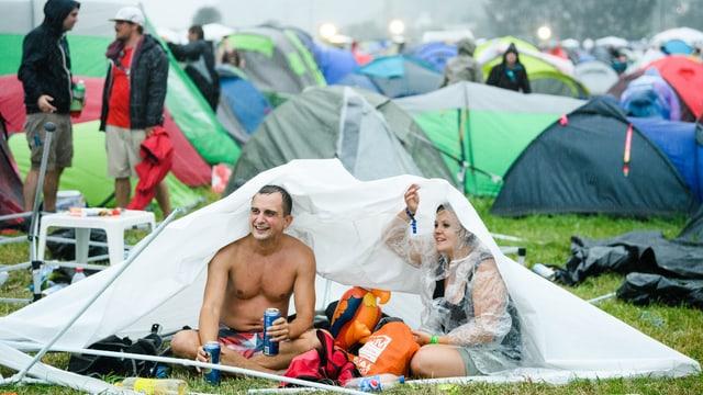 Menschen in Zelt unter Regen.