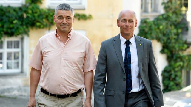 Zwei Männer gehen lächelnd. Der eine mir rosa Hemd und grauweissem Haar, der andere im Anzug mit Halbglatze