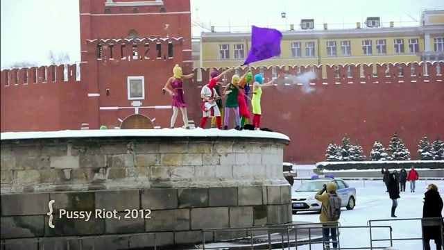 Ein Bild der Gruppe Pussy Riot die auf einer Mauer stehen und eine violette Fahne schwenken.