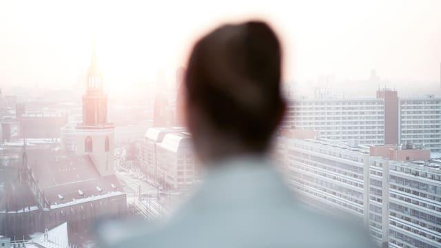 Silhouette einer Frau vor dem Panorama einer Grossstadt.